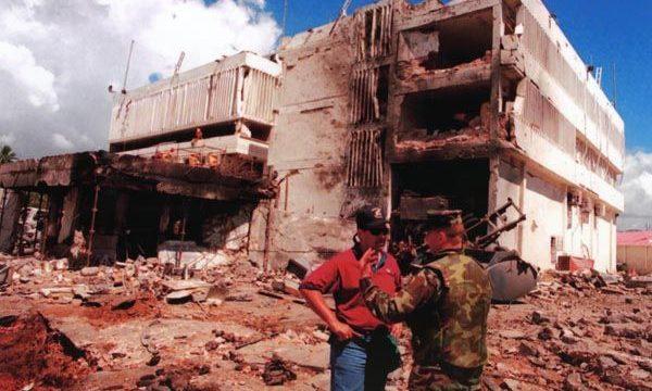 ضابط أمريكي من قوات مشاة البحرية الأمريكية، يتحدث مع ضابط آخر من مكتب التحقيقات الفدرالية الأمريكي. في مدينة دار السلام بدولة تنزانيا، أمام حطام خلفه هجوم القاعدة على السفارة الأمريكية هناك.