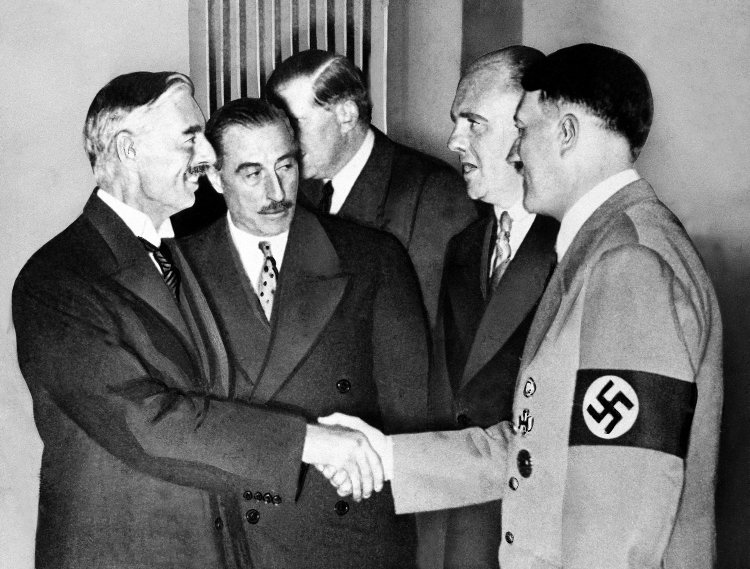 Hands clasped in friendship, Adolf Hitler and England's Prime Minister Neville Chamberlain, are shown in this historic pose at Munich on Sept. 30, 1938. This was the day when the premier of France and England signed the Munich agreement, sealing the fate of Czechoslovakia. Next to Chamberlain is Sir Neville Henderson, British Ambasador to Germany. Paul Schmidt, an Interpreter, stands next to Hitler. (AP Photo)