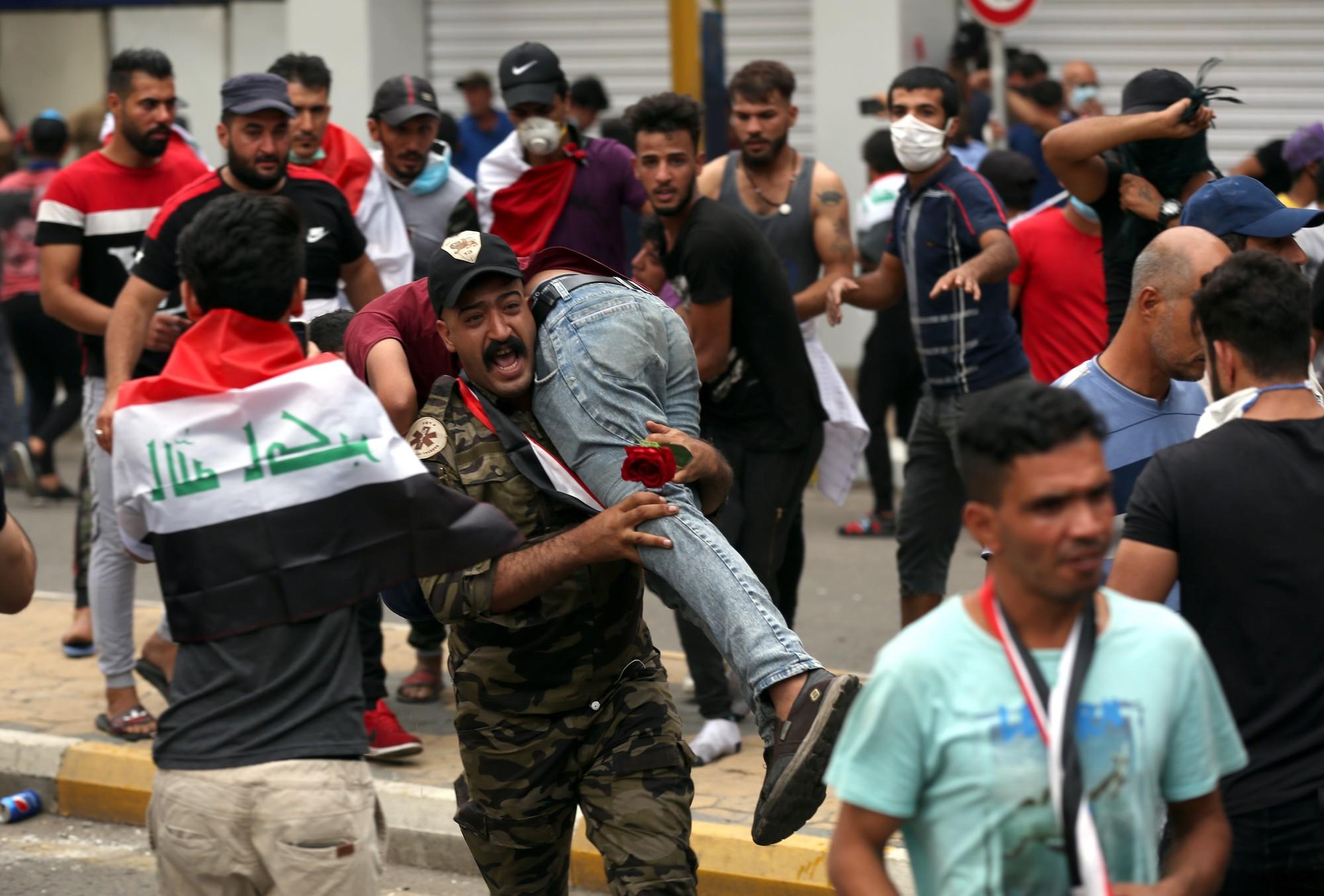 ضابط يحمل مصابا في احتجاجات العراق